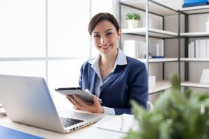 Smiling office worker using a tablet