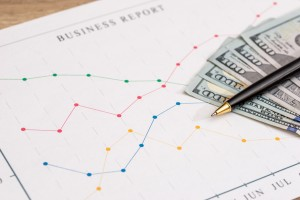 Business charts with dollar, pen on wooden background